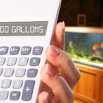 Woman using aquarium volume calculator to determine the water capacity of her fish tank