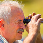 Man looking through eyepiece on optical refractometer to test salinity of his saltwater aquarium