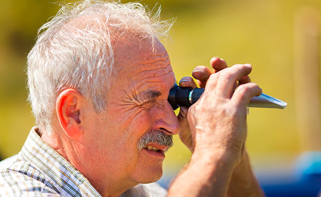 Man looking through eyepiece on optical refractometer to test salinity of saltwater aquarium