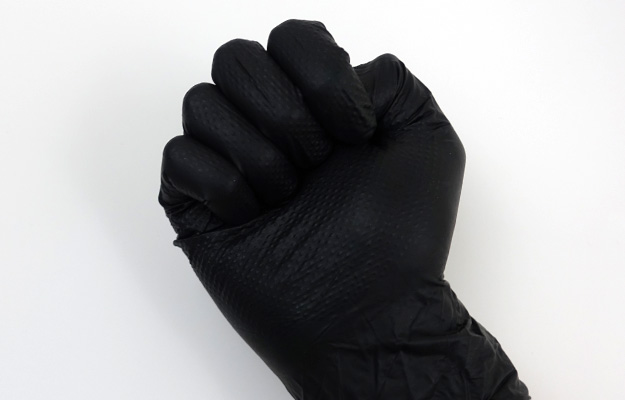 Clenching fist in disposable aquarium gloves to test flexibility