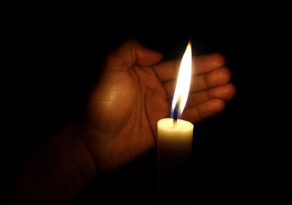 Man holding candle in darkness because of blackout